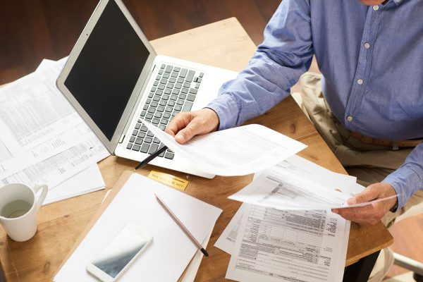 Closeup of unrecognizable senior man filling in application papers at home sitting at table with laptop